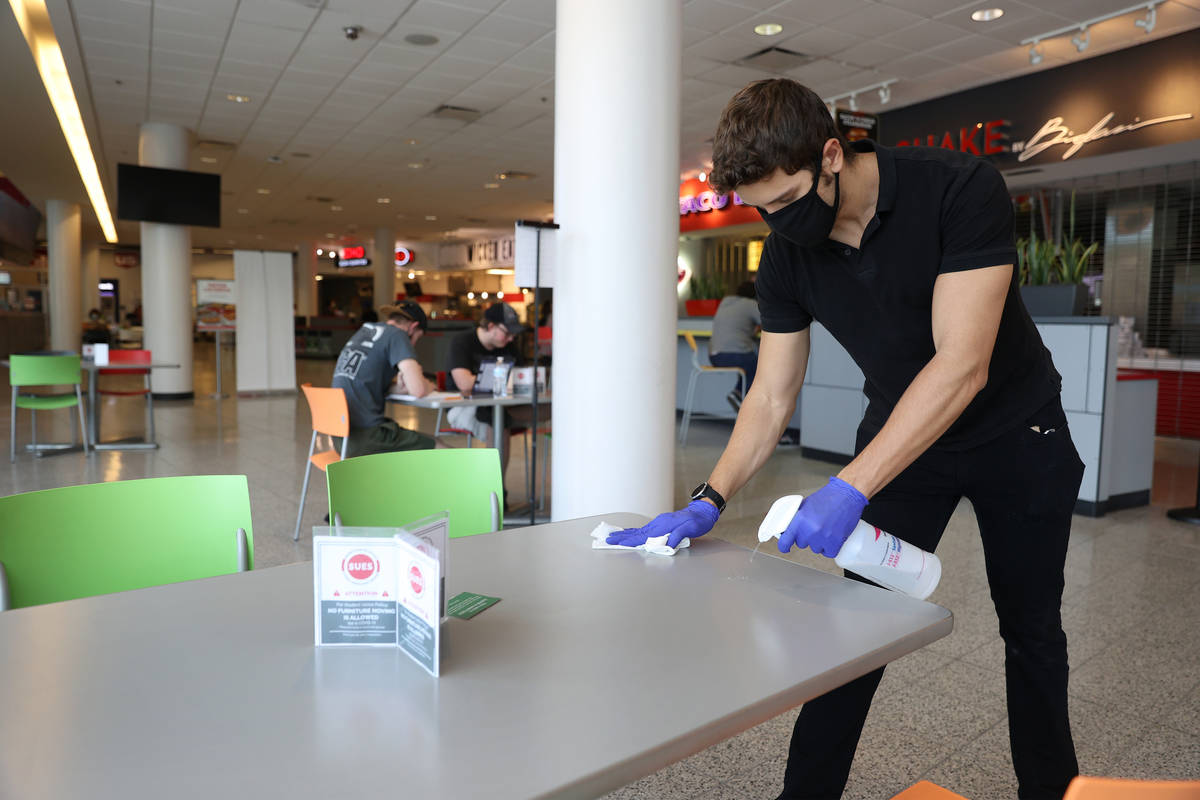 Student worker Christian Quintana cleans a table in the Student Union's food court at UNLV in L ...