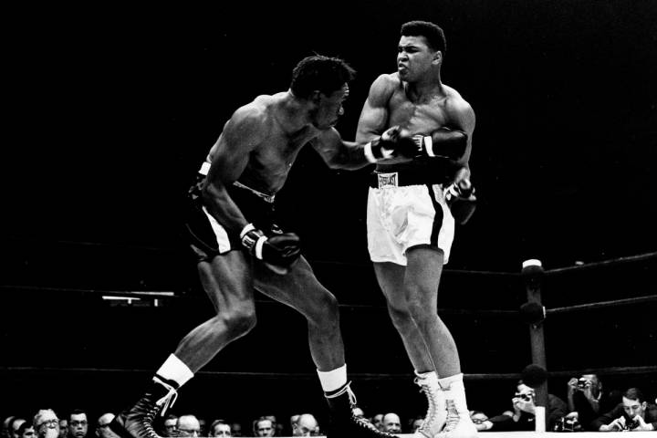 Cassius Clay exchanges punches with Charley Powell in the first round of the scheduled 10-round ...