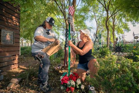 Volunteers Sue Ann Cornwell, left, and Alicia Mierke work on restoring individual memorial trel ...