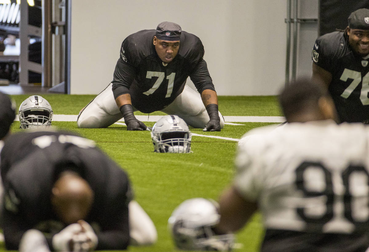 Las Vegas Raiders offensive tackle Denzelle Good (71) stretches with teammates during warm ups ...
