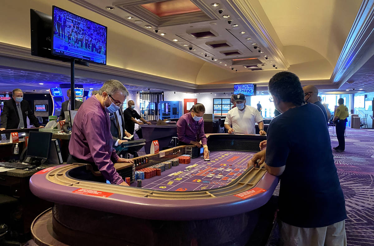 Guests play craps at Harrah's with social distancing as they are open for business again follow ...