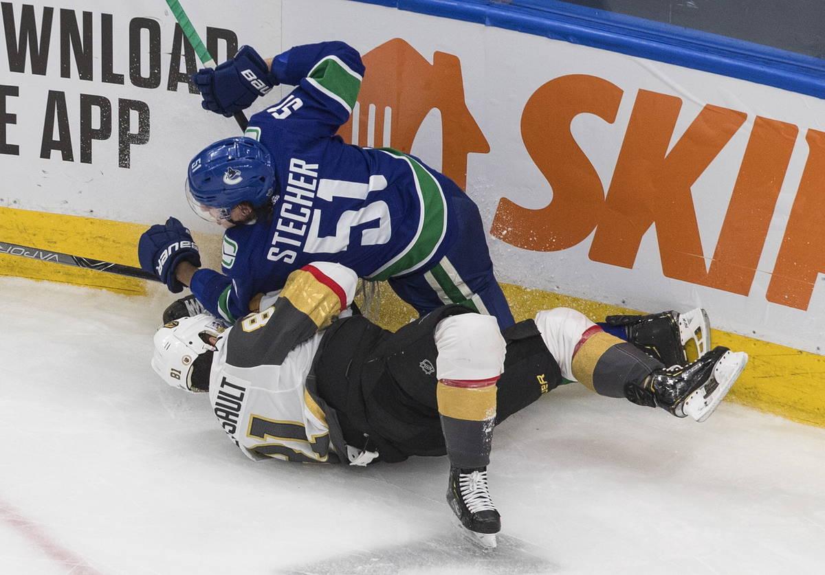Vancouver Canucks' Troy Stecher (51) checks Vegas Golden Knights' Jonathan Marchessault (81) du ...