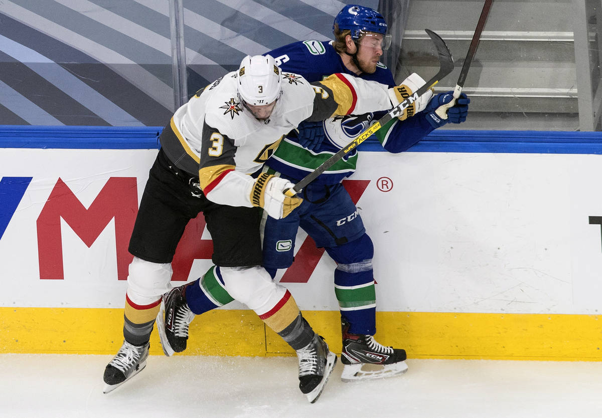 Vancouver Canucks' Brock Boeser (6) is checked by Vegas Golden Knights' Brayden McNabb (3) duri ...