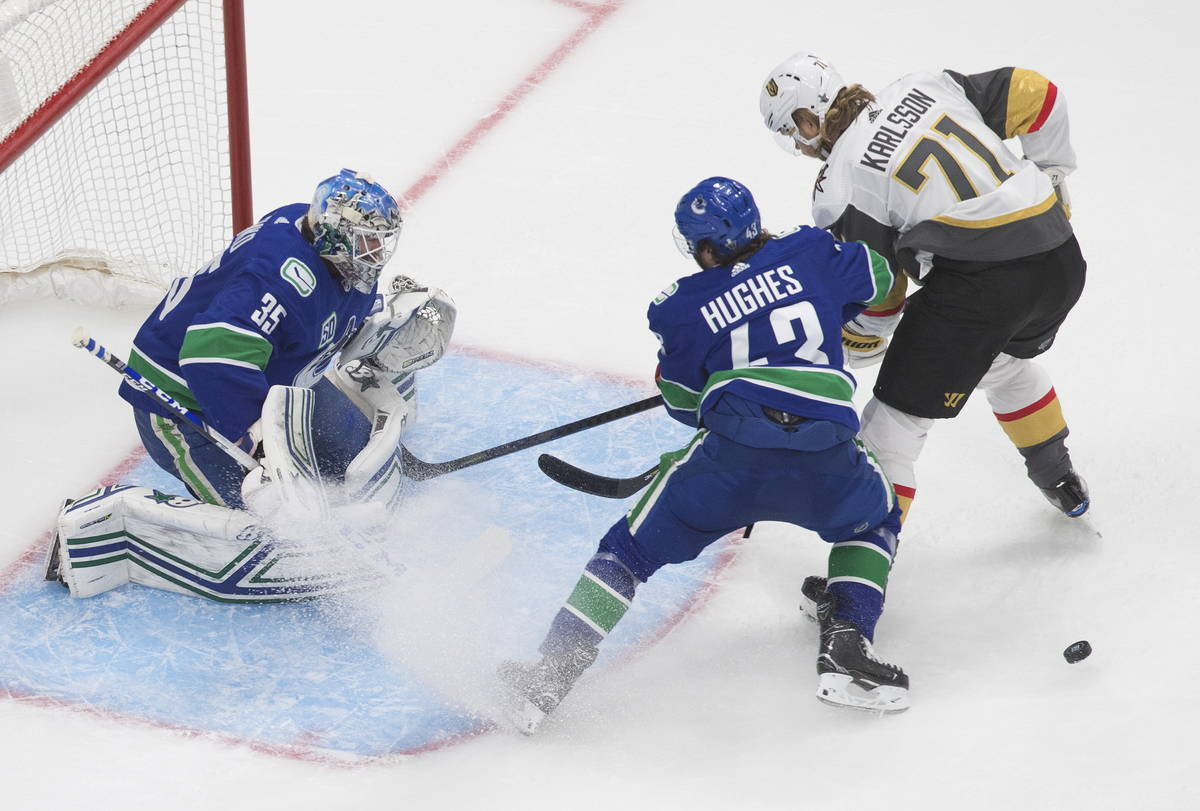 Vancouver Canucks goalie Thatcher Demko (35) makes a save as Vegas Golden Knights' William Karl ...