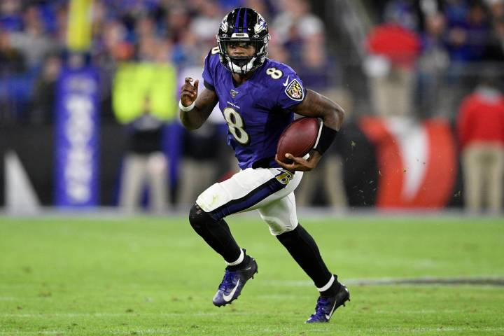 Baltimore Ravens quarterback Lamar Jackson (8) scrambles during the second half of an NFL divis ...