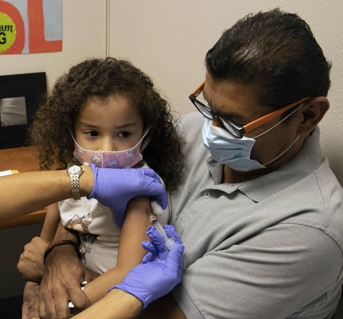 Roberto Lopez holds his daughter, Jasmin Moreno, 4, as Victoria Hodge, licensed practical nurse ...