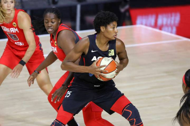 Las Vegas Aces' Angel McCoughtry (35) spins past the defense of Atlanta Dream's Shekinna Strick ...