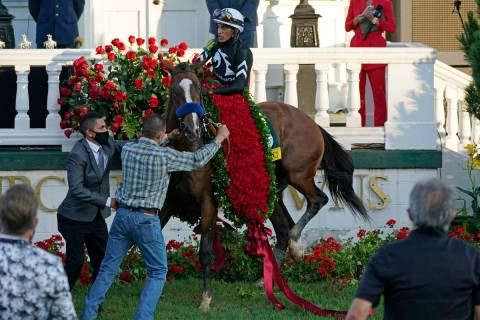 Jockey John Velazquez attempts to control Authentic in the winners' circle after winning the 14 ...