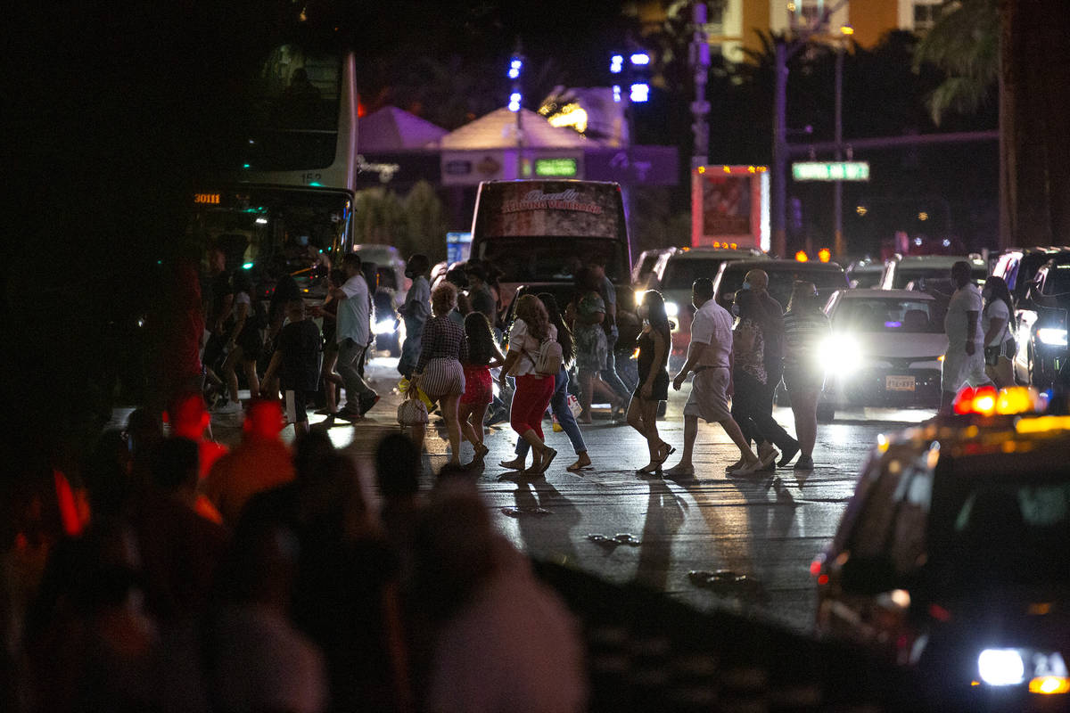Visitors cross Las Vegas Boulevard on the Strip during Labor Day weekend on Saturday, Sept. 5, ...