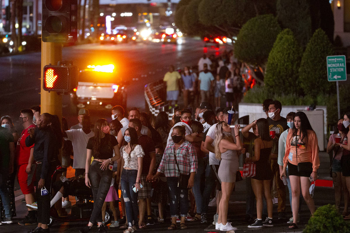 Visitors wait to cross the street outside Caesars Palace on the Strip during Labor Day weekend ...