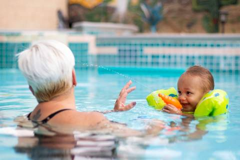 King Carter, 1, sprays his grandma, Tina Carter, with a squirt gun in their backyard pool on Su ...