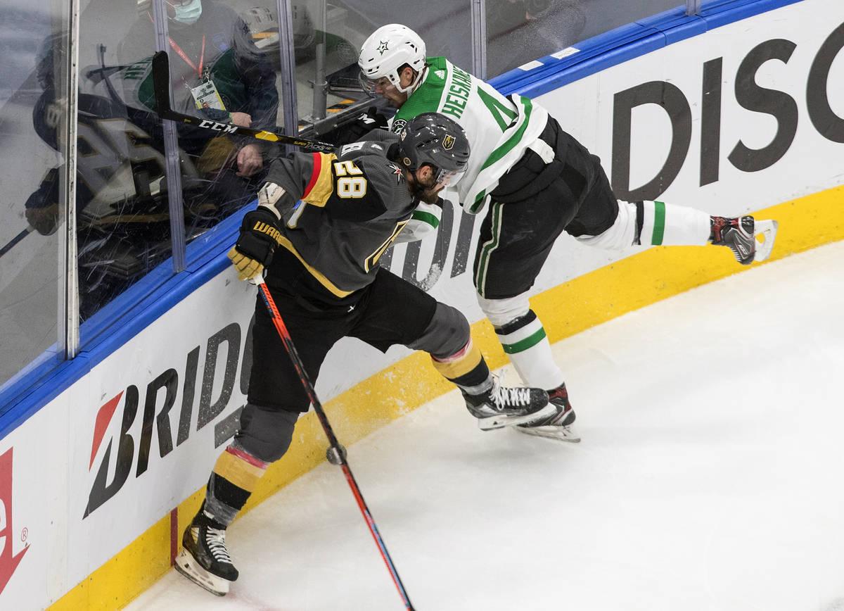 Vegas Golden Knights' William Carrier (28) checks Dallas Stars' Miro Heiskanen (4) during the s ...
