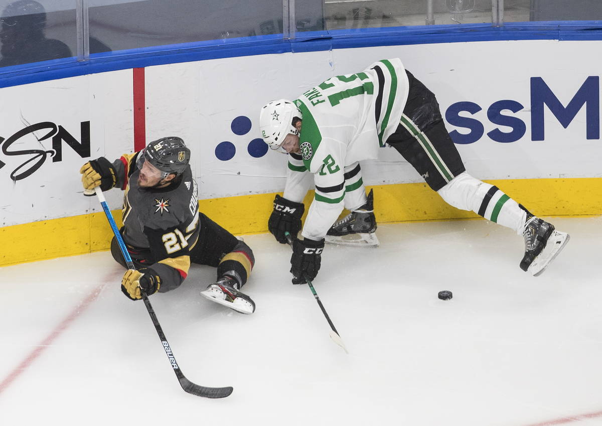 Vegas Golden Knights' Nick Cousins (21) is checked by Dallas Stars' Radek Faksa (12) during the ...