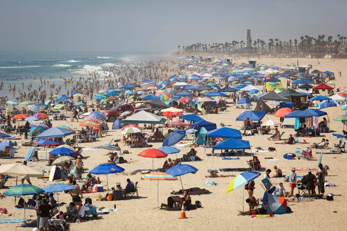 People escape the California heat wave at the beach, Sunday, Sept. 6, 2020, in Huntington Beach ...
