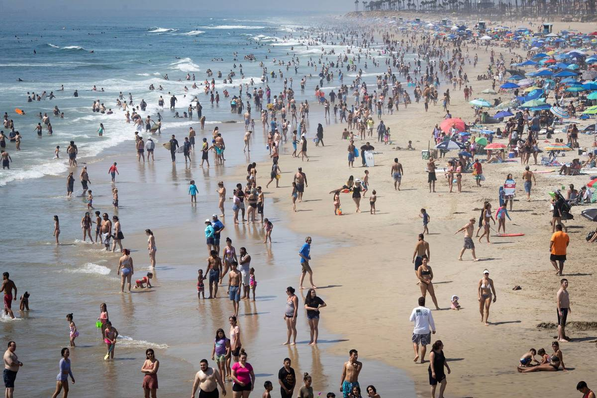 People are seen at the beach during a heat wave, Sunday, Sept. 6, 2020, in Huntington Beach, Ca ...