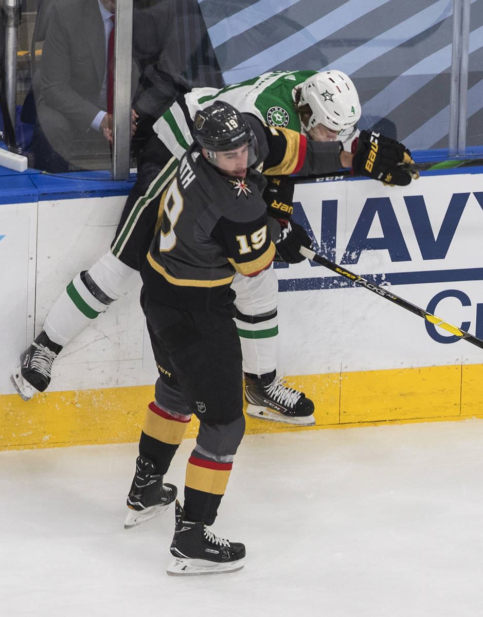 Dallas Stars' Miro Heiskanen (4) is checked by Vegas Golden Knights' Reilly Smith (19) during t ...