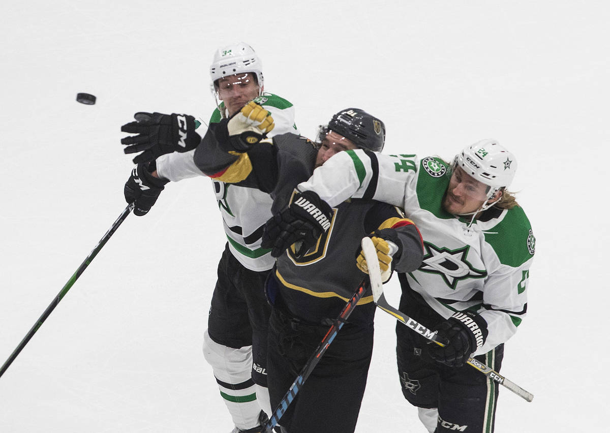 Dallas Stars' Denis Gurianov (34) and Roope Hintz (24) compete for the puck with Vegas Golden K ...