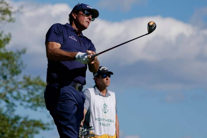 Phil Mickelson watches his tee shot on the 17th hole in the first round of the Northern Tr ...