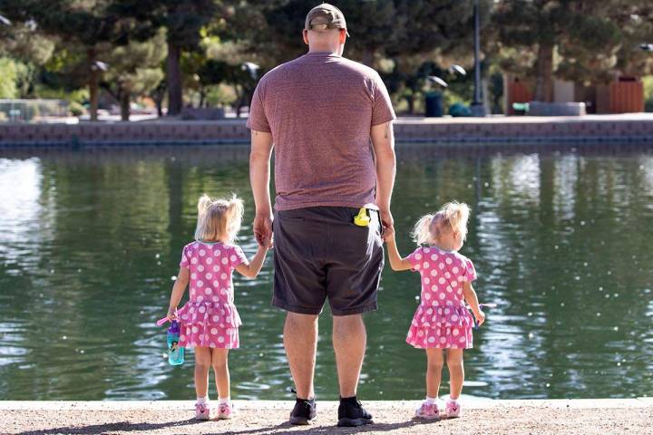 Derrick Agnew relaxes with his daughters Penelope, 3 , left, and Eloise, 2, at Sunset Park on T ...