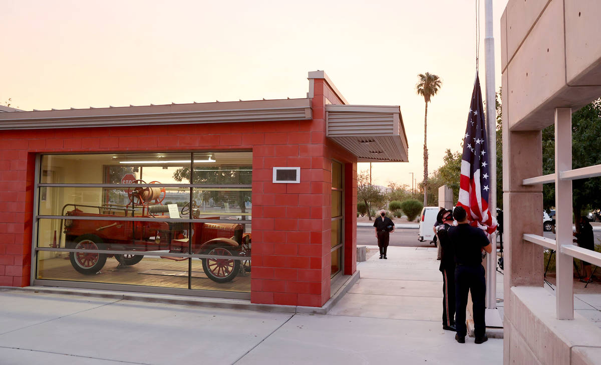 Firefighters take the flag down in preparation for raising a flag that flew at the World Trade ...