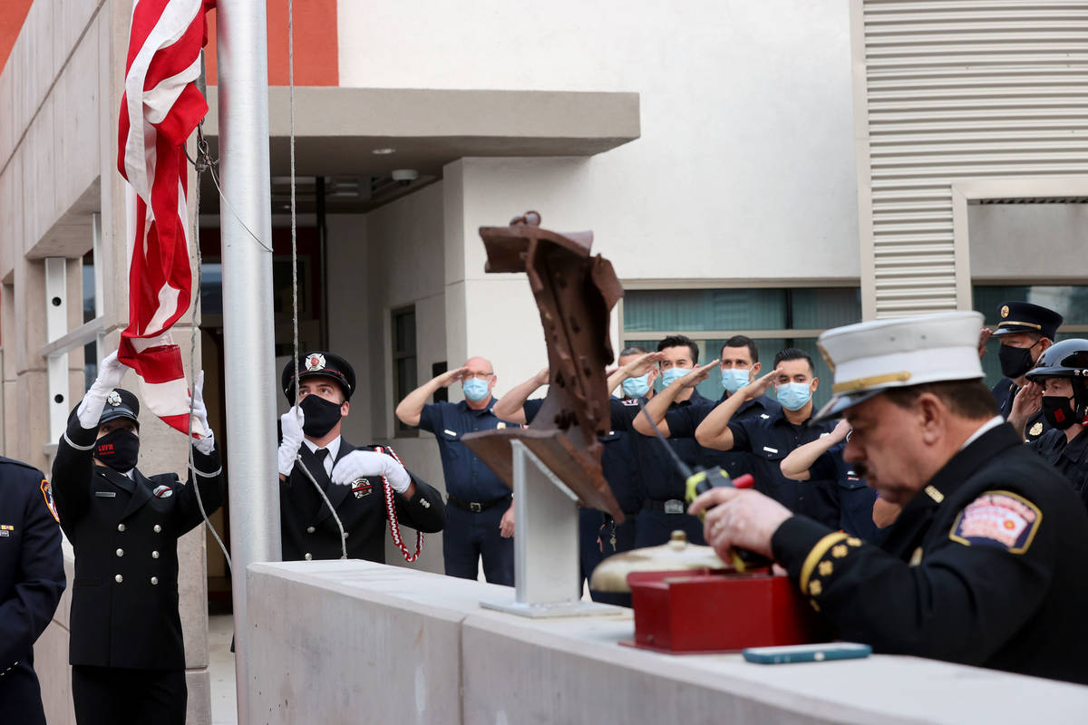 Las Vegas firefighter Lisa Leonard, left, and engineer Brian Dietz raise a flag that flew at th ...
