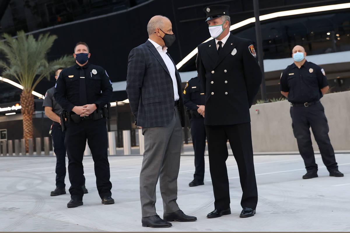 Las Vegas Raiders President Marc Badain, left, speaks to Clark County Fire Department Firefight ...