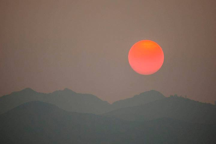 The sun, clouded by smoke from wildfires in California, sets behind Spring Mountains National R ...