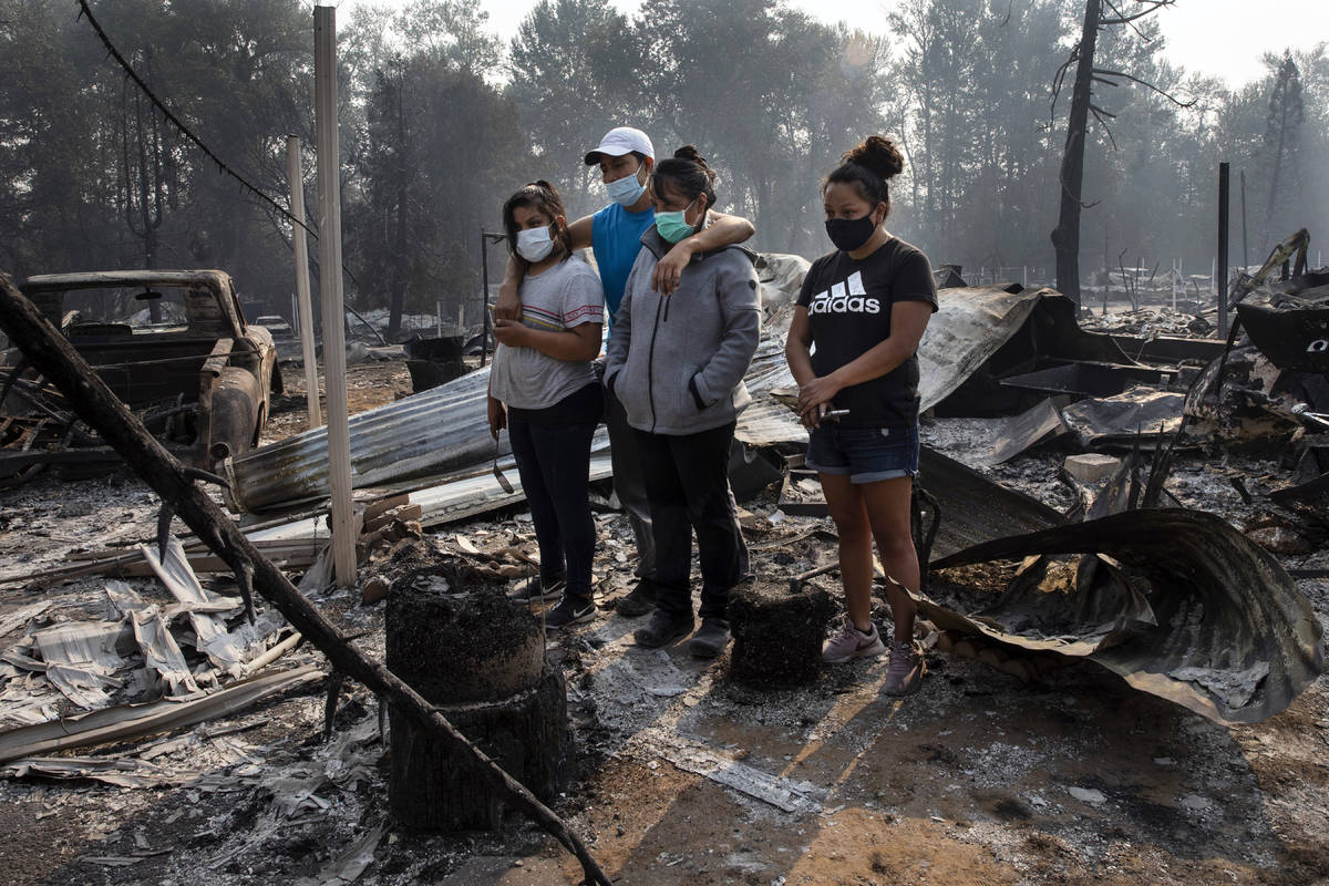 The Reyes family looks at the destruction of their home at Coleman Creek Estates mobile home pa ...