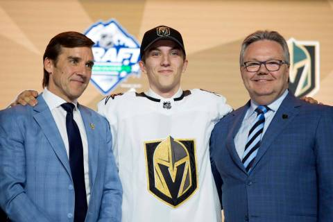 Vegas Golden Knights pick Peyton Krebs, center, poses during the first round of the NHL hockey ...