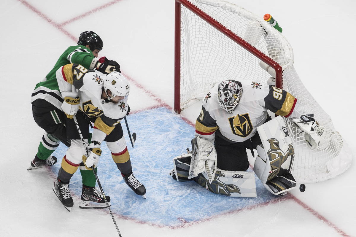 Dallas Stars' Jamie Benn and Vegas Golden Knights' Shea Theodore (27) work in front of Golden K ...