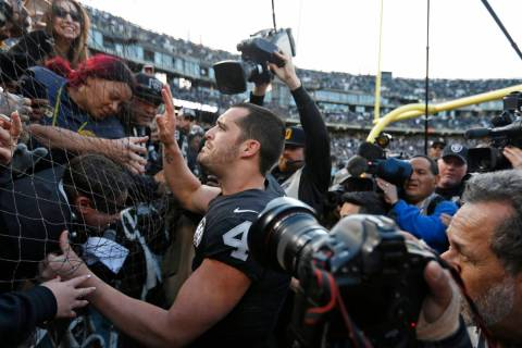 "Oakland Raiders quarterback Derek Carr is greeted by fans in ""The Black Hole"" after a ..."