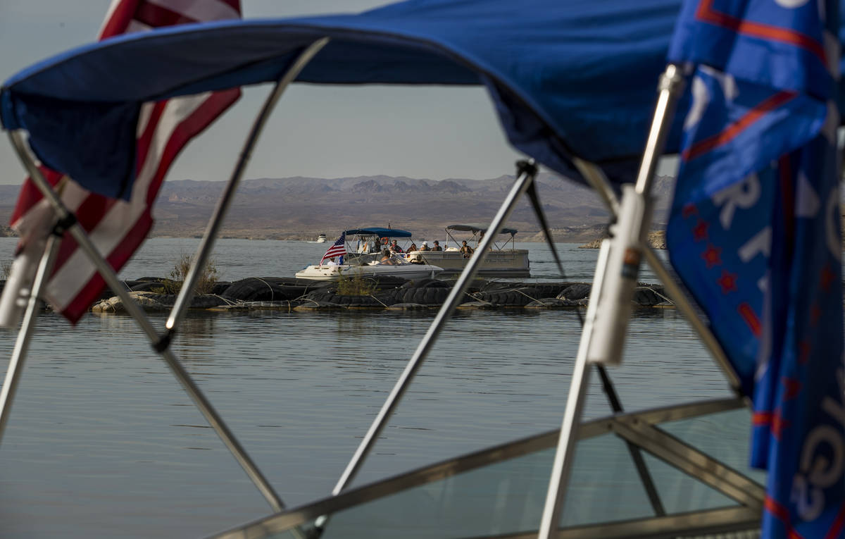Two boats pass as some boats are already prepared for the President Donald Trump boat parade Sa ...