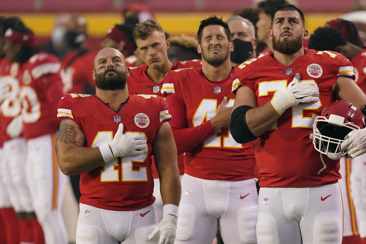 Kansas City Chiefs players stand for the national anthem before an NFL football game against th ...