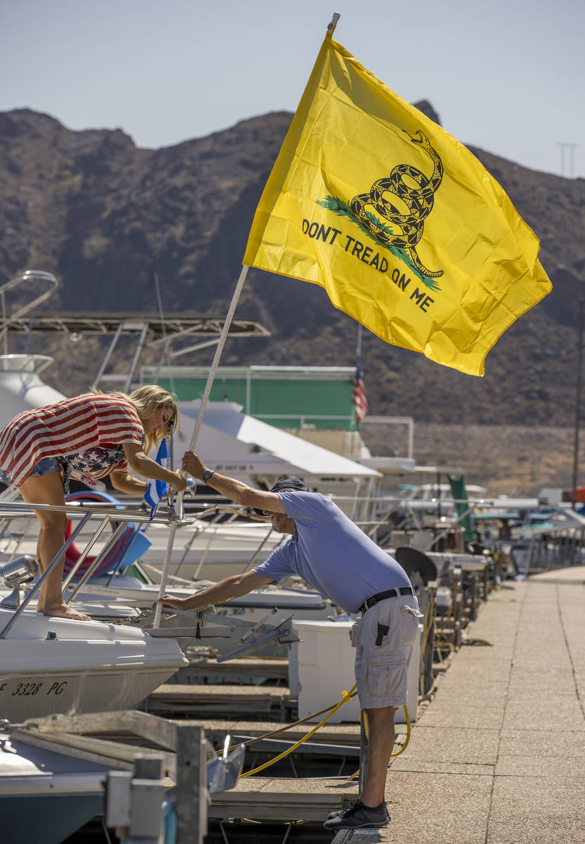 Event organizer Christine Snedden, left, helps to secure a flag with Jerry Dusa as they prepare ...