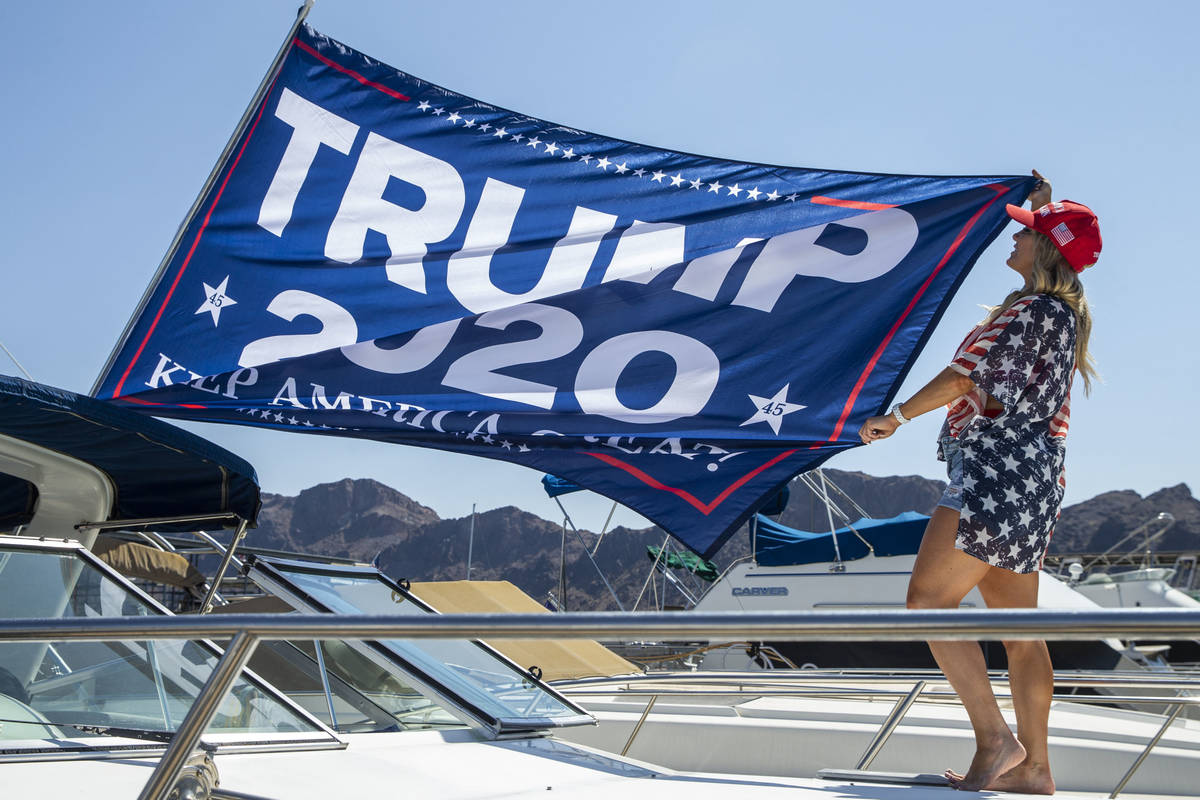 Event organizer Christine Snedden unfurls a flag as she and others prepare their boat for the P ...