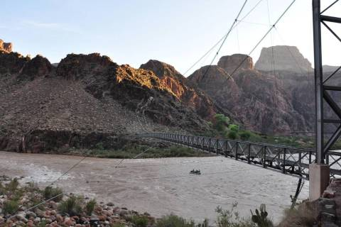Boaters on the Colorado River pass under the Silver Bridge while getting an early start on thei ...