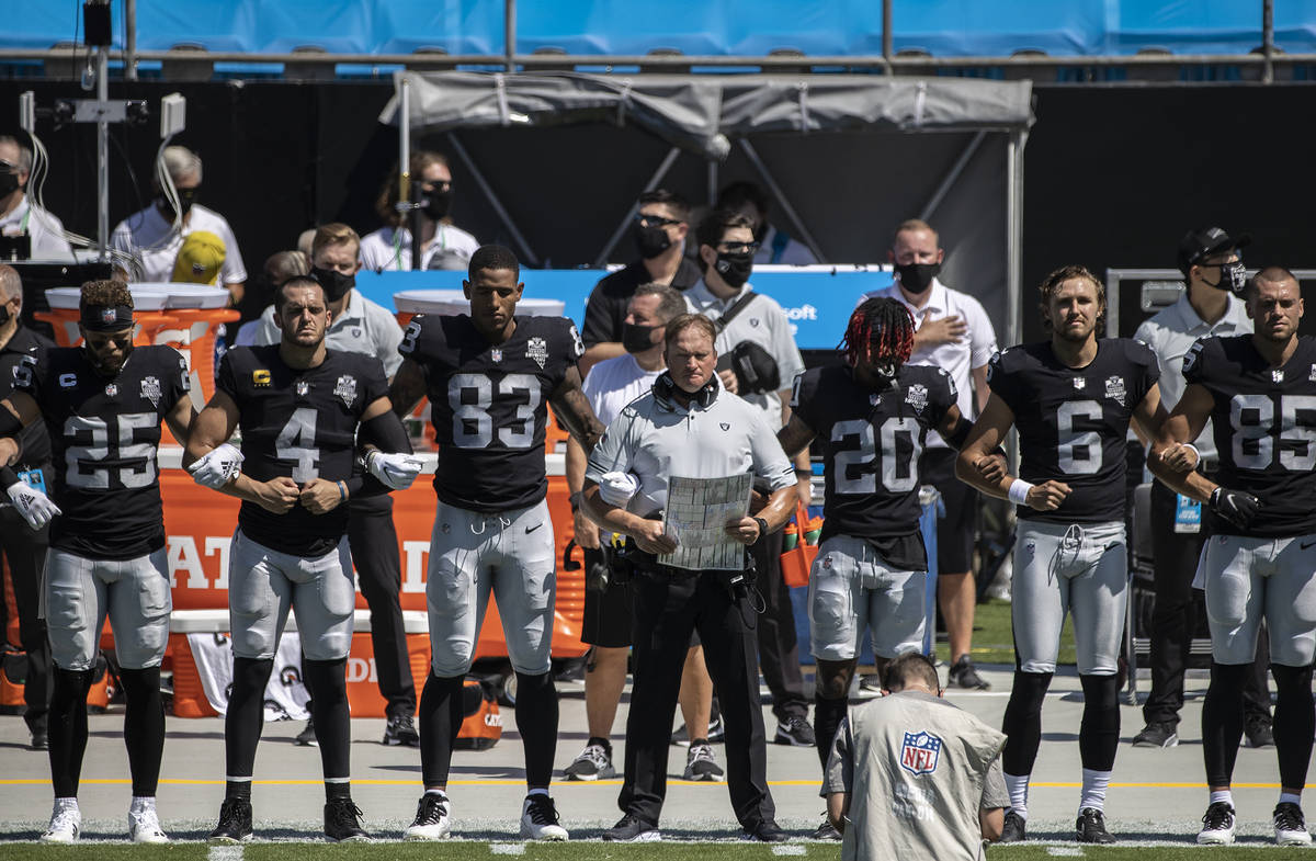Las Vegas Raiders head coach John Gruden, middle, locks arms with his players during the nation ...
