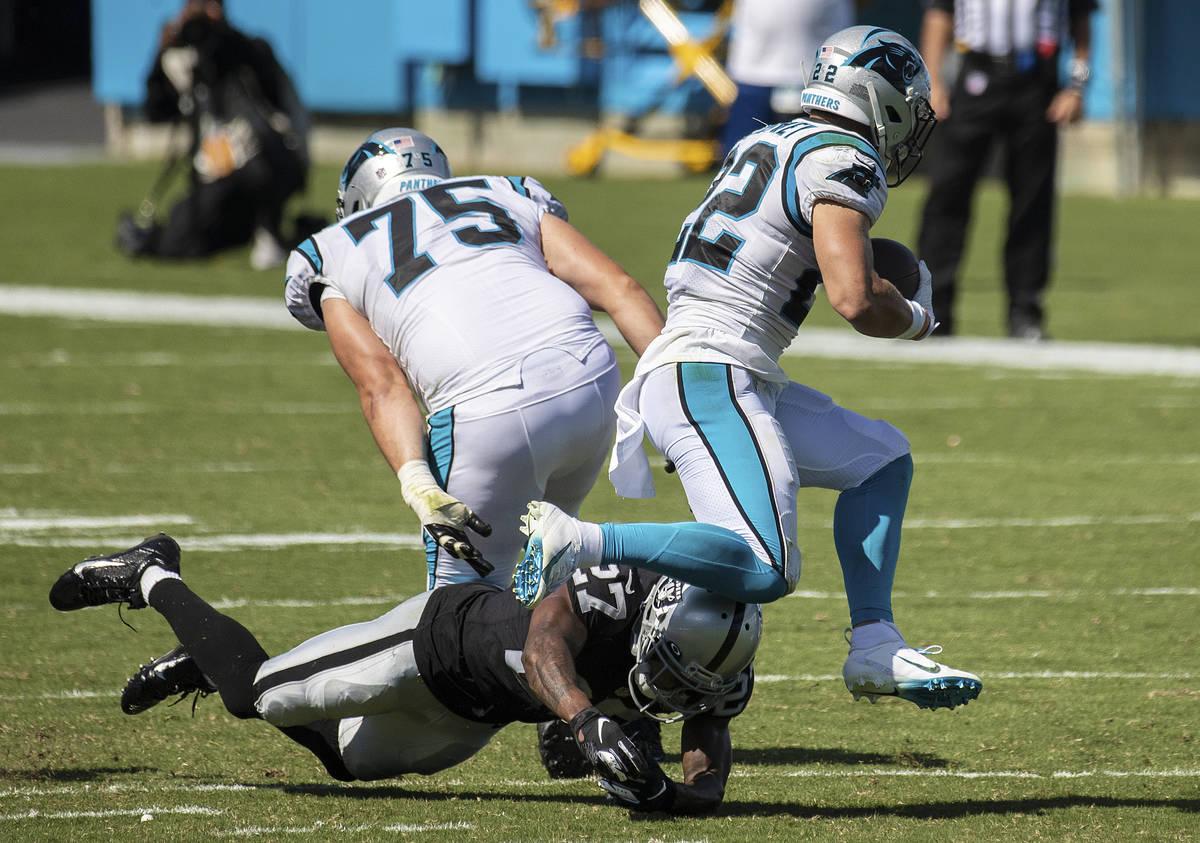Carolina Panthers running back Christian McCaffrey (22) leaps over Las Vegas Raiders cornerback ...