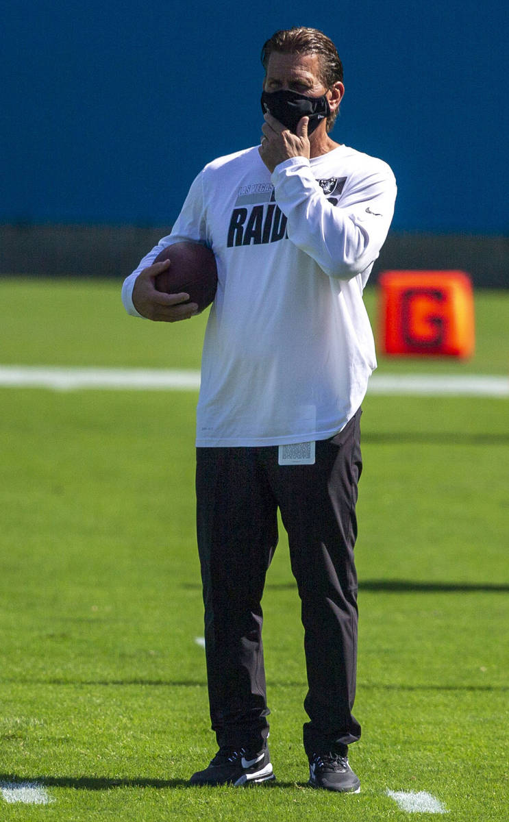 Las Vegas Raiders offensive coordinator Greg Olson adjusts his face mask before an NFL football ...