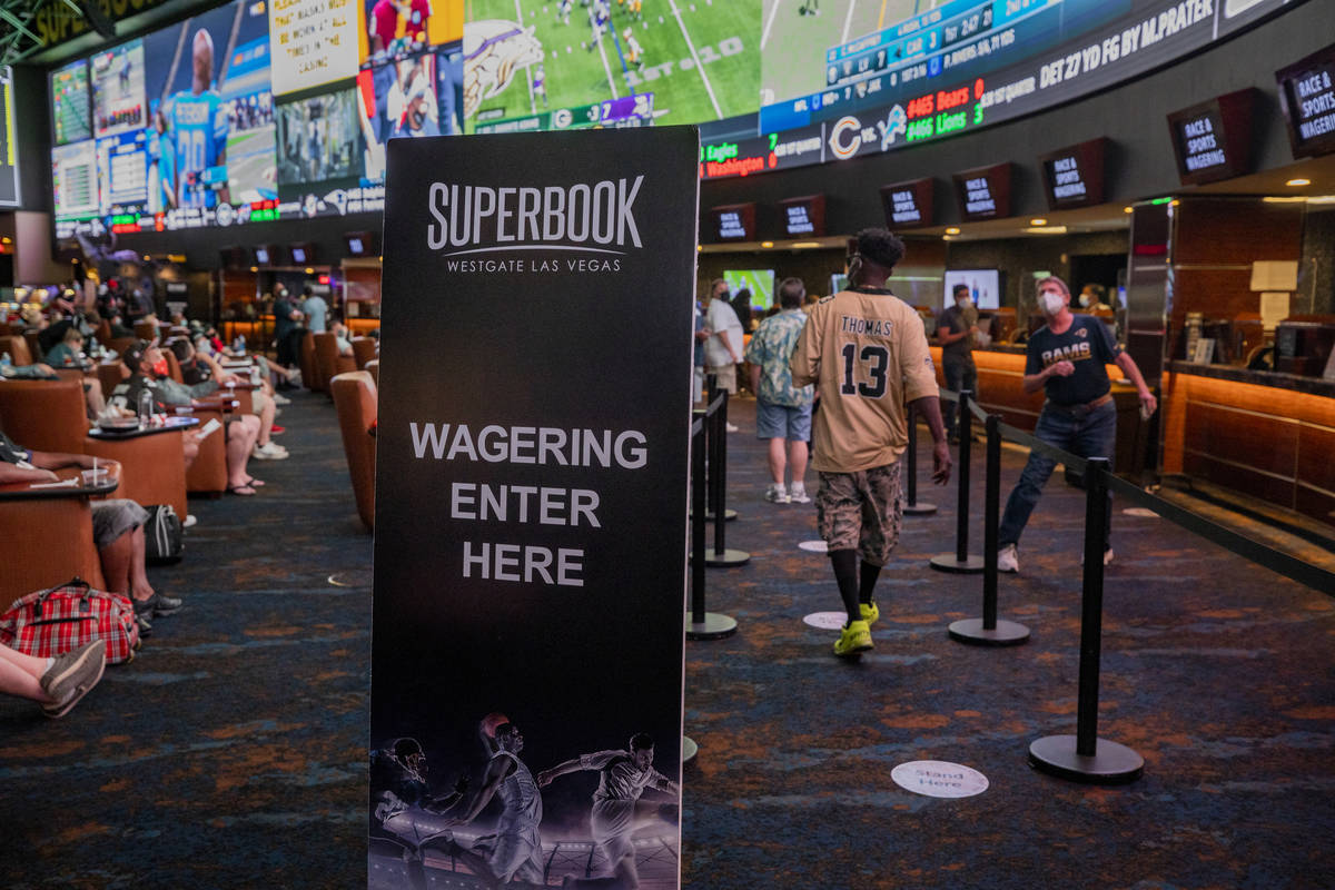 Individuals watch games and place bets at the Westgate Sportsbook during opening weekend, in La ...