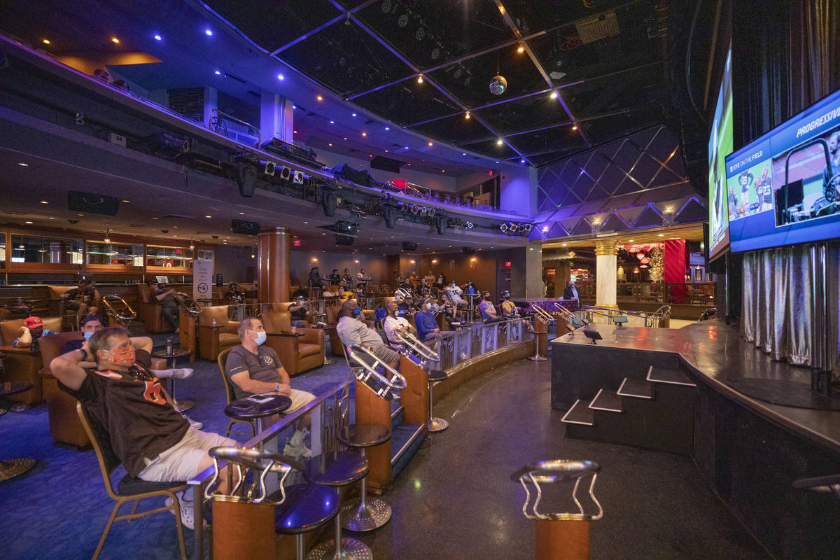 Individuals watch games while sitting six feet apart in the Westgate Cabaret, in Las Vegas on S ...