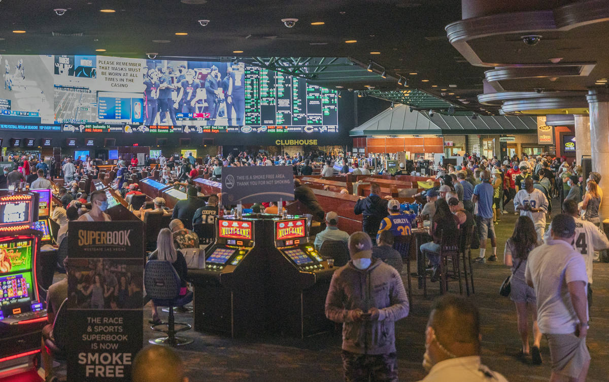 Individuals watch games at the Westgate Sportsbook during opening weekend, in Las Vegas on Sund ...