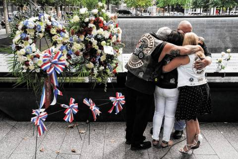 Mourners hug beside the names of the deceased Jesus Sanchez and Marianne MacFarlane at the Nati ...
