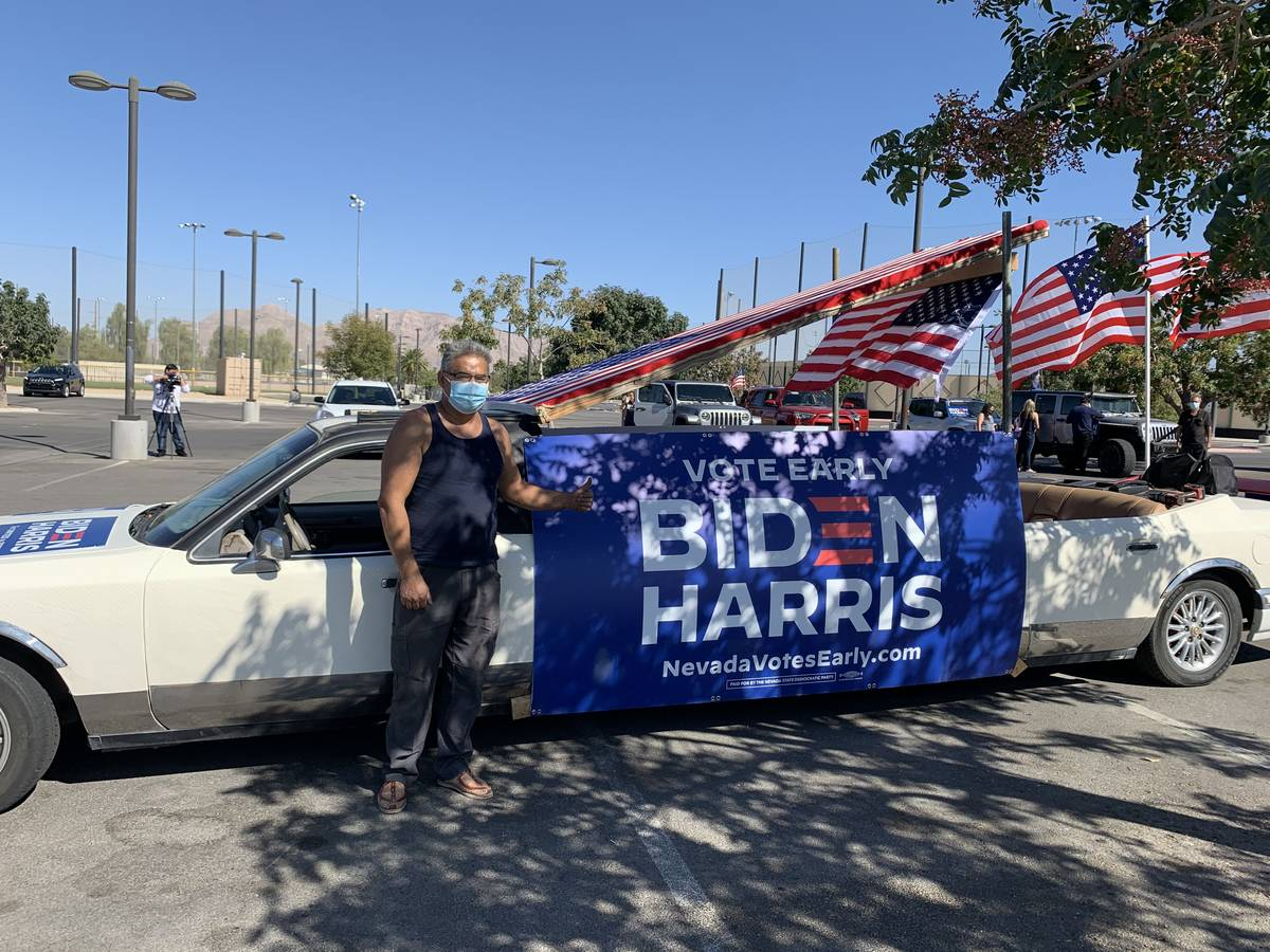 Eddie Ramos poses in front of his old limousine, which he covered in posters and American flags ...
