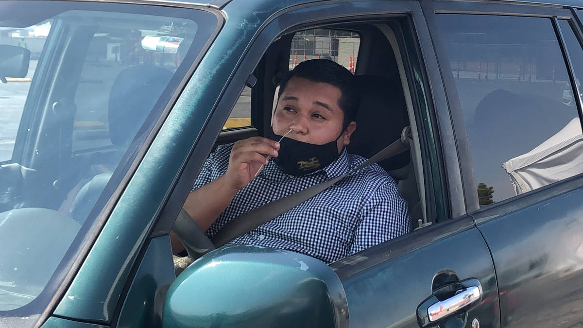 """Vincent Nava swabs his nose during his COVID-19 test at the """"Stop, Swab & Go!"""" drive-thru testi ..."""