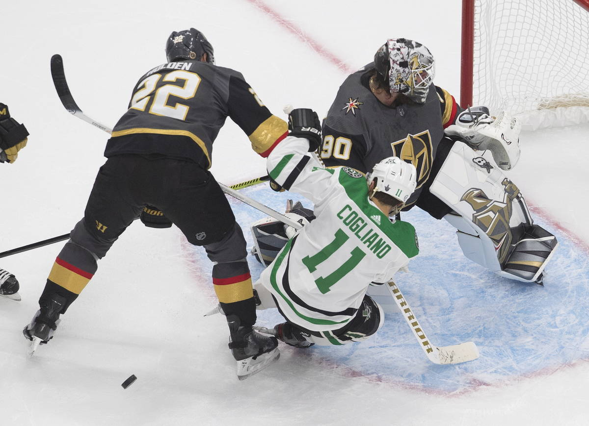 Dallas Stars' Andrew Cogliano (11) and Vegas Golden Knights' Nick Holden (22) battle in front o ...