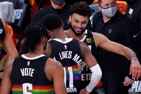 Denver Nuggets' Jamal Murray, right, celebrates with Monte Morris (11) after an NBA conference ...