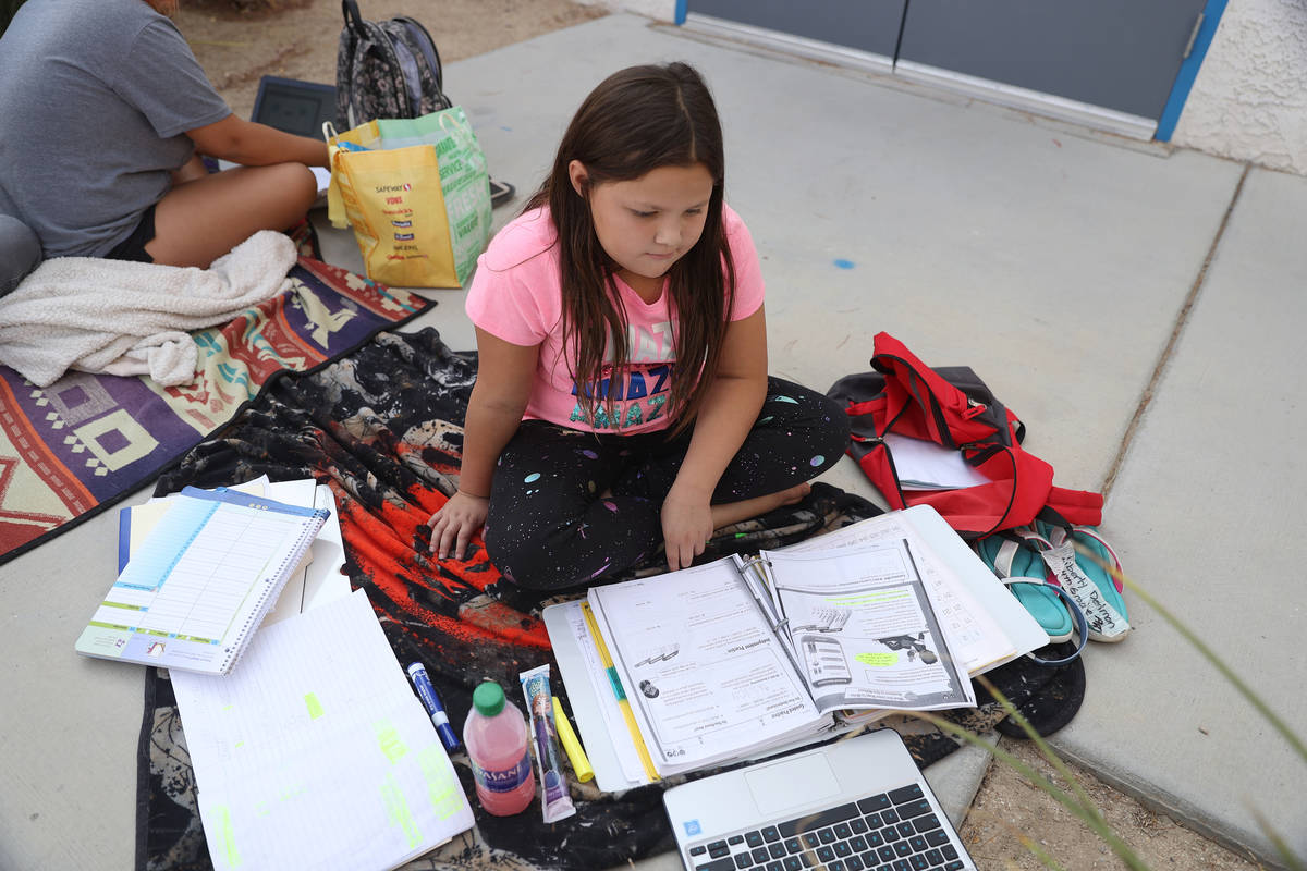 Liberty Dedmon, 9, participates in her virtual class using the school Wi-Fi outside of Indian S ...