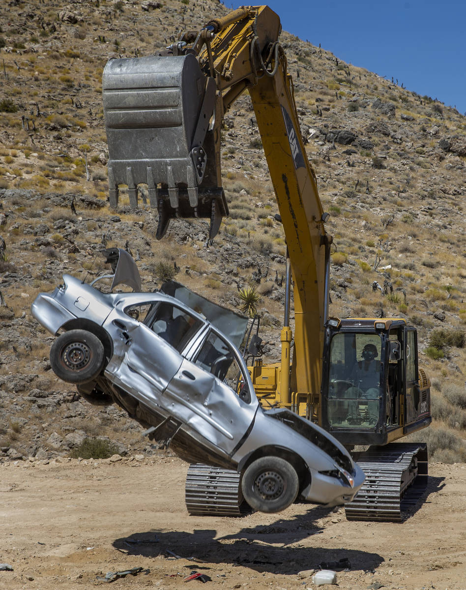 Christopher Lawrence releases a car from the bucket of a Caterpillar Excavator, one of the extr ...