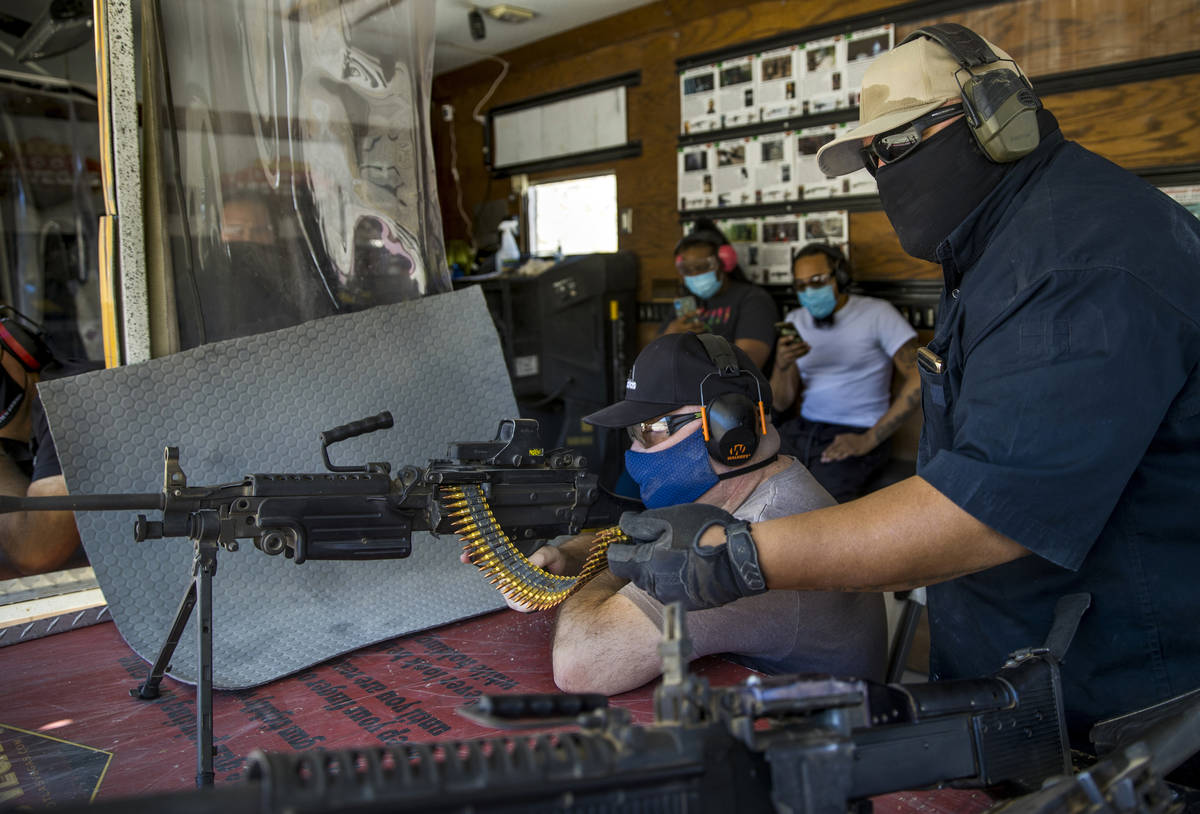 Christopher Lawrence, center, fires an M249 Saw machine gun assisted by Sam Davidson on the Adr ...